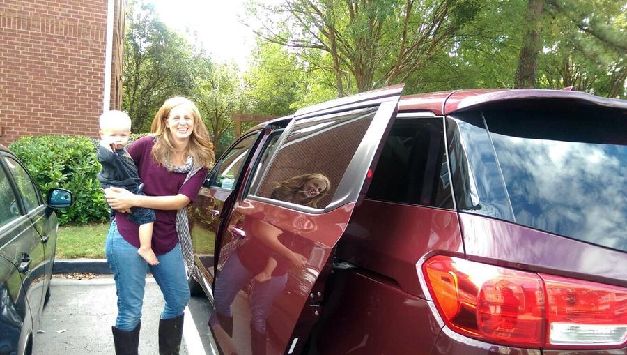 Cait Montoya with Kia Sedona Van and child