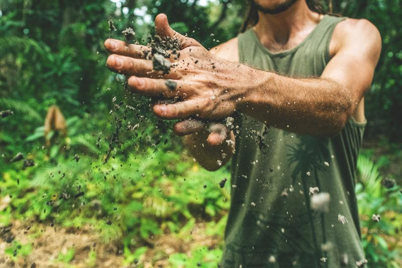 man rubbing dirt together in hands in forest