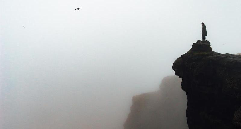 looking out to the horizon over a foggy cliff