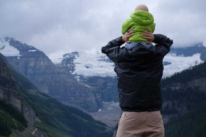 baby on shoulders looking at mountain