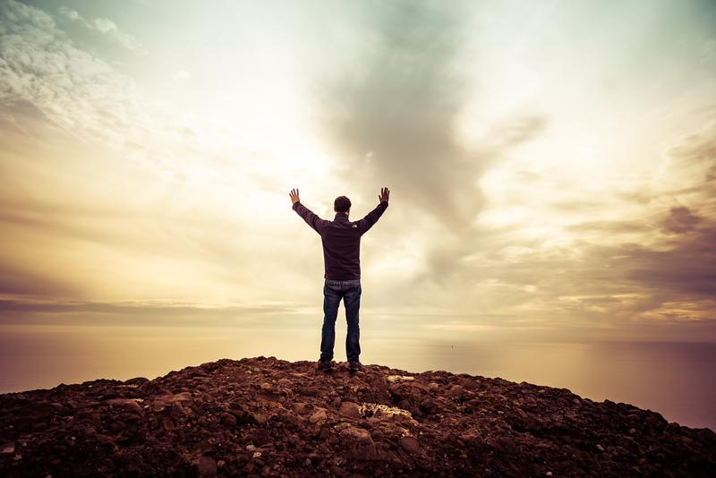 Man standing on hill raising hands to the sky