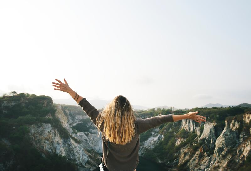 woman throwing her arms up in celebration looking out over cliff