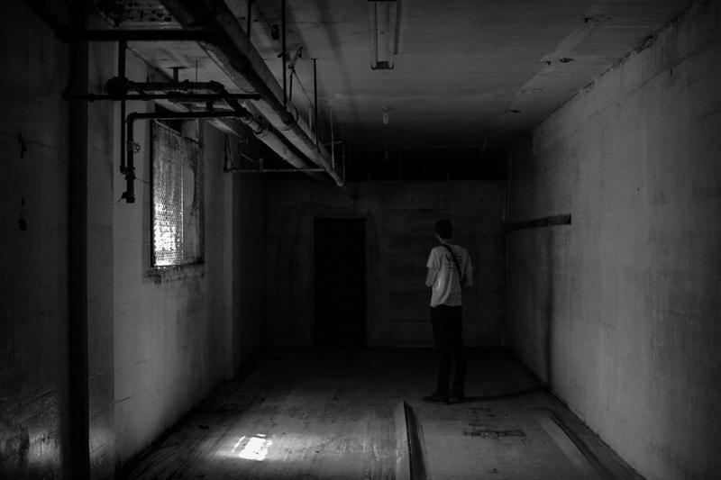 Man facing a dark door in a basement