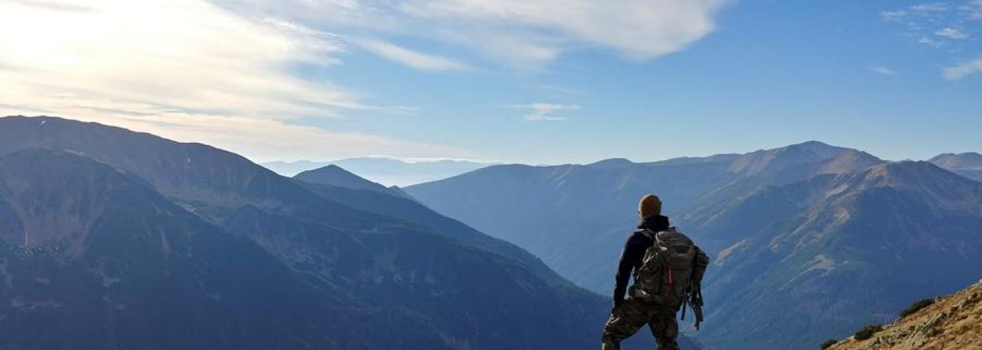 adventure: man standing on the edge of a cliff looking out at the mountains