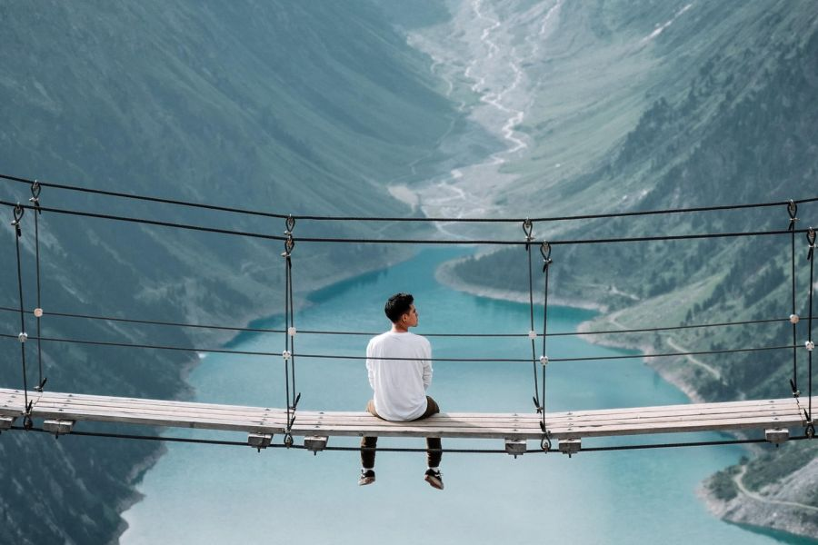 man sitting on a rope bridge looking out at the mountain