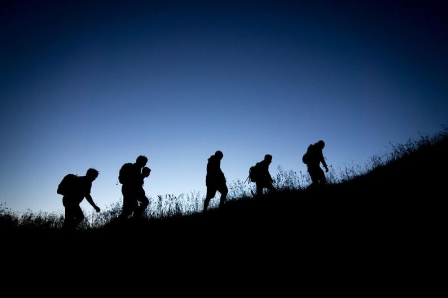 Group of people hiking up hill in the dark